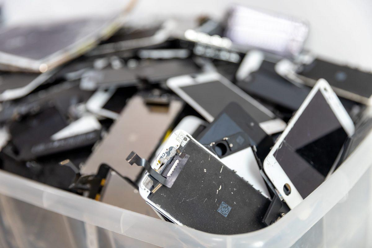 old and broken smartphones in plastic box