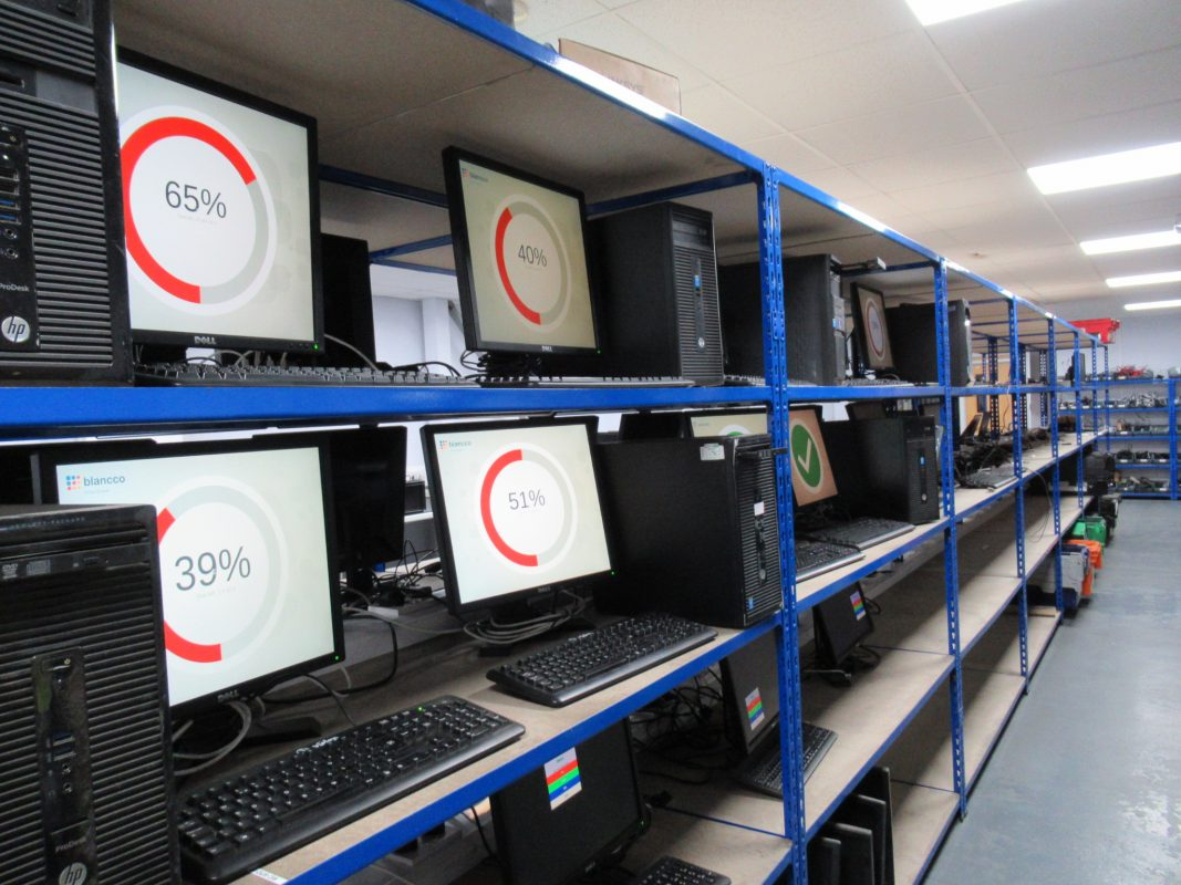 Laptops on shelves being data wiped using Blancco software