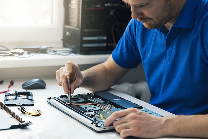 man wearing blue shirt repairing laptop on desk